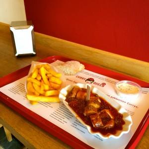 Currywurst, Pommes, Trüffelmayo und Brot auf dem Tablett