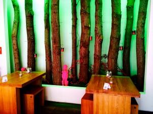 Wand mit Baumstämmen und kleiner Buddha-Figur