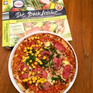 fertige Pizza Spargel Schinken auf einer Hälfte mir Mais bestreut