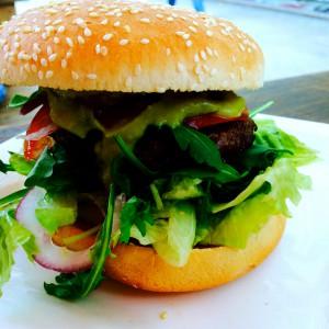 Close-up vom Avocado Burger wobei das Fleisch kaum zu sehen ist, dafür die Avocado-Creme und der Salat umso deutlicher