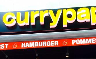 Burger und Pommes mit der Fassade vom Currypapa