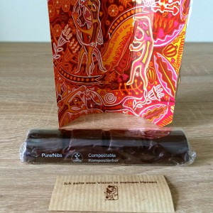 Aufgestellte Verpackung, in Zellulosefolie gehüllter Riegel und Spruchzettel