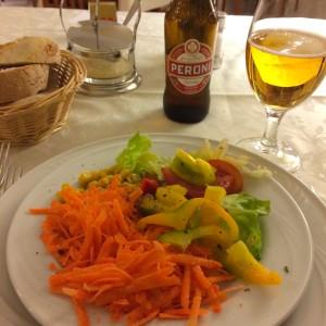 Salatteller mit Peroni Bier im Hintergrund