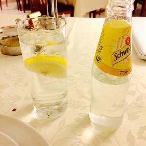 Volles Glas Gin Tonic und eine halbvolle Schweppes Flasche