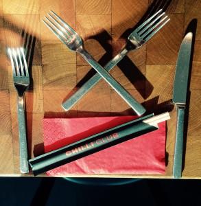 Gedeck mit Messer, Gabel und Stäbchen und gekreuzte Gabeln