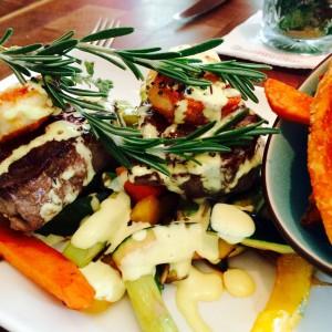zwei Stücke Rind und 2 Garnelen auf Gemüse mit einer Schale Süßkartoffelchips