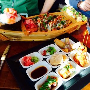 9 Schälchen mit Tapas und ein Sushi Schiff