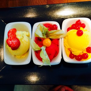 drei Sorbetschalen mit etwas Obst