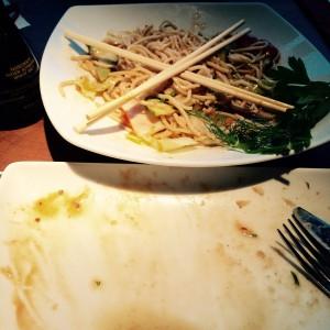 Ein leerer Teller und ein Teller mit Woknudeln und gekreuzten Essstäbchen