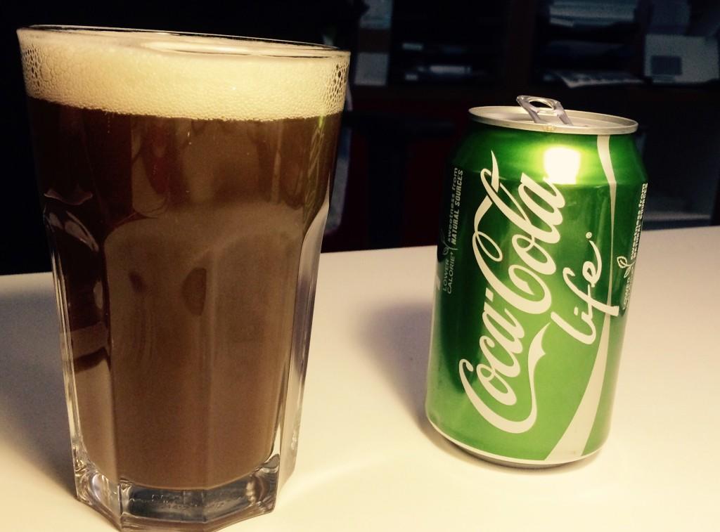 Glas mit Cola-Weizen und Coca Cola Life Dose daneben