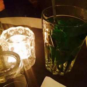 Glas mit heissem Minztee und Kerzenlicht