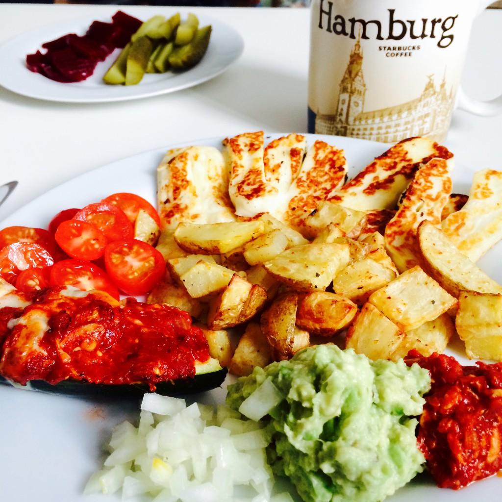 Teller mit  Halloumi, Tomaten, Avocado- und Tomatendip, Kartoffelwedges und Zwiebeln - Hamburg Tasse im Hintergrund und saure Gurken und rote Bete - Veegie Day