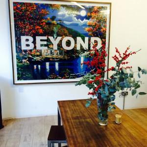 """Tisch mit Blumen, Wandbild mit Aufschrift """"beyond"""""""