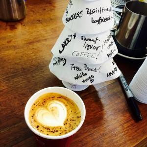 Cappuccino mit Herzmuster im Milchschaum und ein Papiertannenbaum mit Wünschen