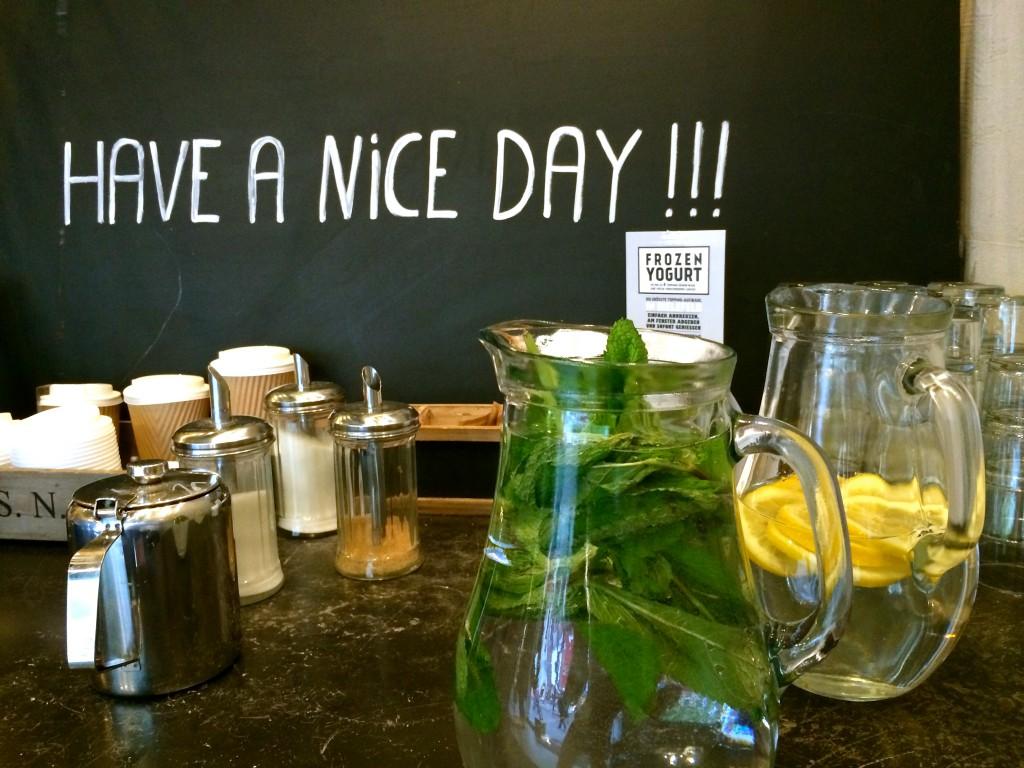 """Frisches Minz- und Zitronenwasser, Zucker, Pulver, Deckel und """"Have a nice Day!!!"""" Schild im Hintergrund"""