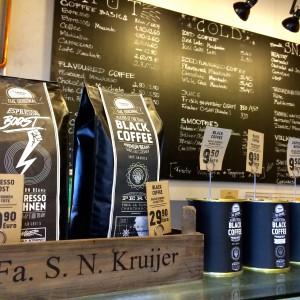 Kaffeebeutel und -dosen, Menütafel im Hintergrund