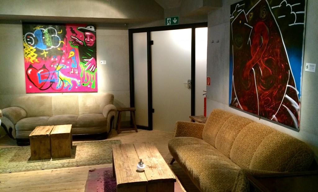 Zwei Sofas mit Tischen, zwei Bilder an der Wand und der Toiletteneingang - Ozone Bielefeld
