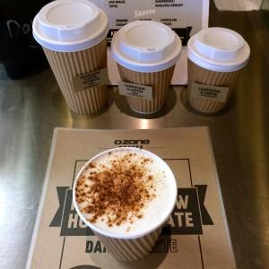 Cappuccino von oben mit Schokopulver, die drei unterschiedlich großen To-Go-Becher im Hintergrund