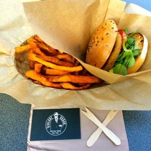 Süßkartoffel-Fritten, veganer Burger, gekreuzte Holzgabeln und Vincent Vegan Visitenkarte