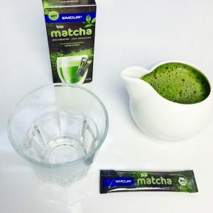 Emcur Matscha in der Kanne, leeres Glas, Dosierstick und Verpackung