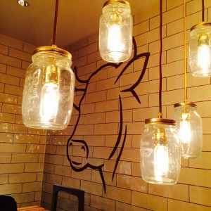 Lampen aus Konservengläsern mit Wandzeichnung Rinderkopf im Hintergrund