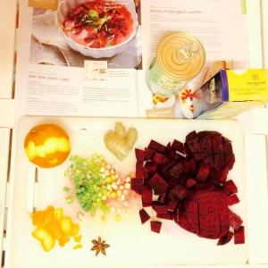 Zutaten der Alnatura Rote Beete Suppe auf einem weißen Schneidebrett, aufgeschlagenes Magazin