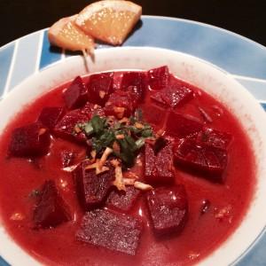 Teller mit Rote Beete Suppe, fein gehackten Frühlingszwiebeln/Orangen Schnitze und geviertelten Orangenscheiben als Deko