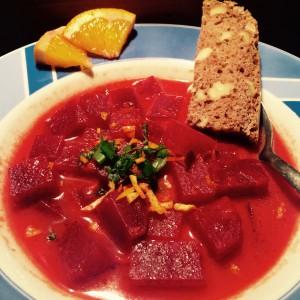 Teller mit Rote Beete Suppe, fein gehackten Frühlingszwiebeln/Orangen Schnitze und geviertelten Orangenscheiben und einem Stück Brot als Deko