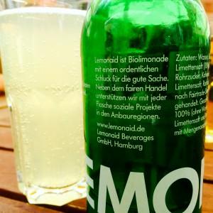 Leere LemonAid Flasche, volles Glas