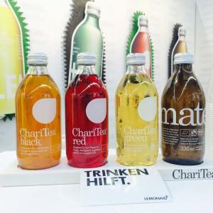 """Die 4 Sorten/Flaschen ChariTea mit einem Sticker """"Trinken hilft"""""""