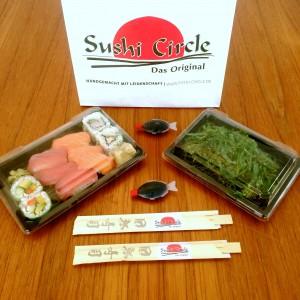 Eine Sushi Box, ein Wakamesalat, zwei Sojasoßen-Fische, zwei Paar Essstäbchen und die Tüte vom Sushi Circle Hamburg