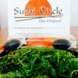 Grüner Wakamesalat mit zwei Sojasoßen-Fischen und der Tüte von Sushi Circle Hamburg