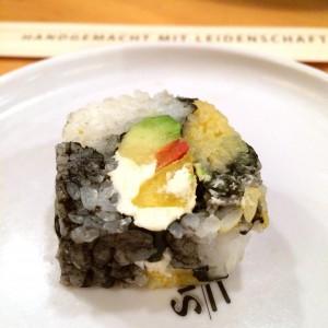 Sushirolle mit weiß-gelb-schwarz gefärbtem Reis, Avocado, Paprika und Creme