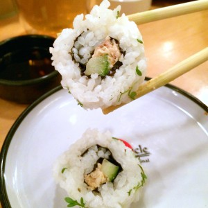 Zwei Sushi-Rollen mit Lachs und Gurke, eins von zwei Stäbchen gehalten