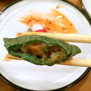Etwas unscharfe, abgebissene, grüne Gemüsetasche bei der man die Füllung erahnen kann zwischen zwei Stäbchen