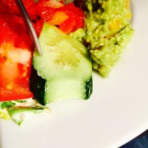 An den Rändern vertrocknete Gurkenscheibe, Tomate und Guacamole im Hintergrund
