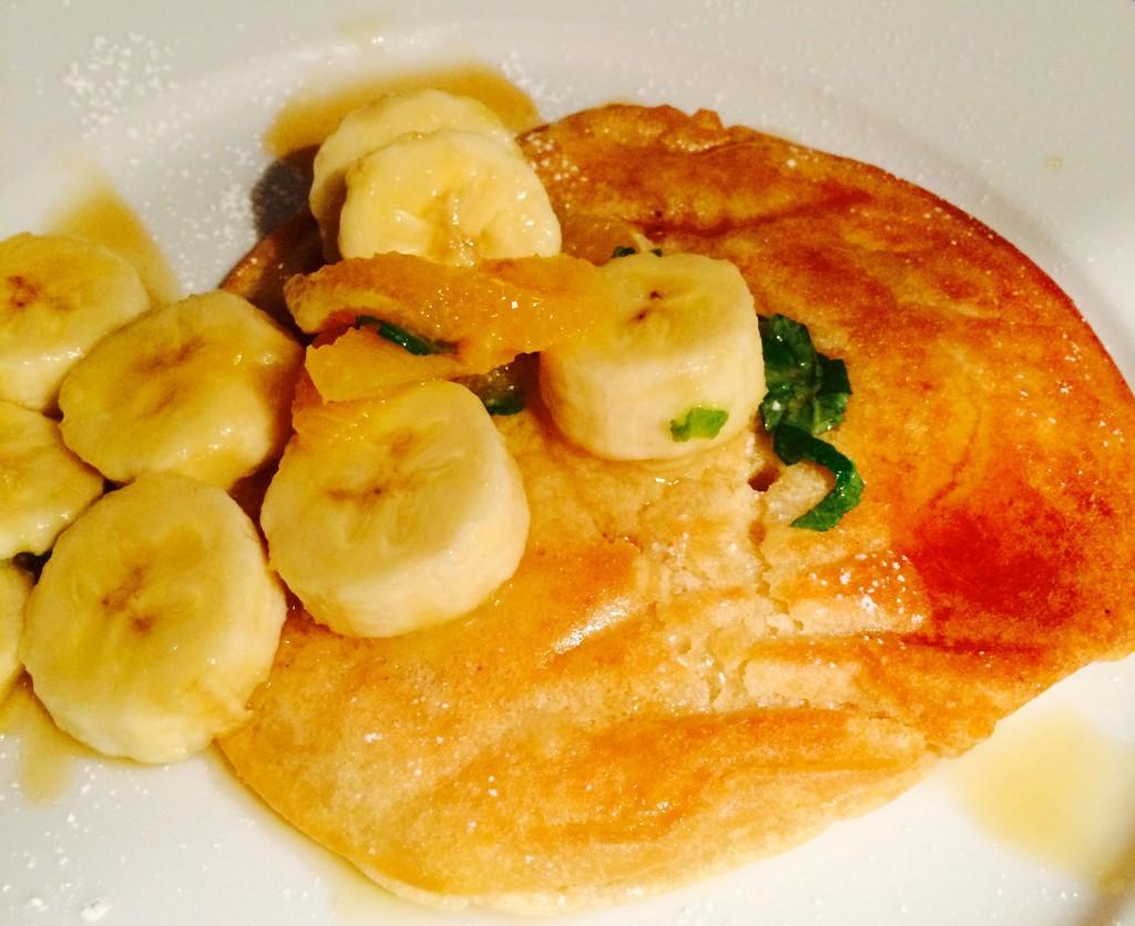 Pancake mit Bananenstücken, durchtränkt von Ahornsirup mit Minze