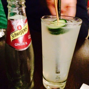 Moscow Mule im Glas mit Gurke, Schweppes Ginger Beer Flasche daneben