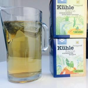 Glaskanne mit -gefärbten- Teewasser, daneben die zwei Boxen