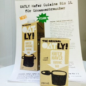 Oatly Hafer Cuisine im kleinen Päckchen vor dem Flyer für die Packung für Großverbraucher