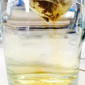 Teebeutel gibt sichtbar Aroma ins Wasser der Glaskanne