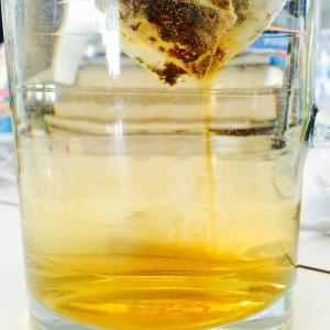 Schwarzteebeutel gibt sein Aroma sichtbar in das Wasser der Glaskanne