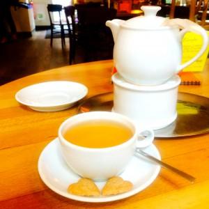 Grüner Tee in der Tasse mit zwei Herzkeksen, Kanne auf Stöfchen im Hintergrund
