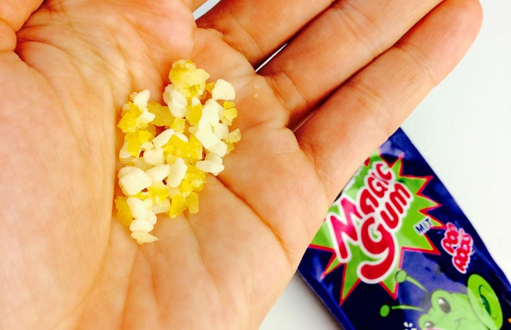 Magic Gum Bröckel in der Hand, Verpackung im Hintergrund
