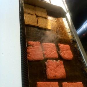 Grill mit quadratischen Fleischfrikadellen und Toastbrot