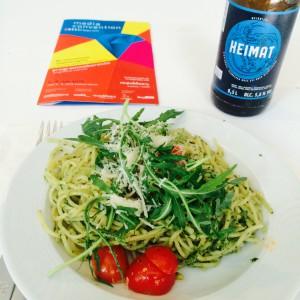 Pesto Spaghetti mit Rucola, Cherrytomaten und Parmesan, daneben das Heimat Bier und ein Programmheft