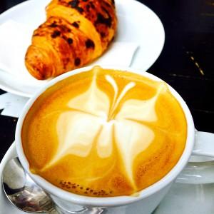 Cappuccino mit Schmetterlingmuster im Milchschaum, Schokocroissant im Hintergrund