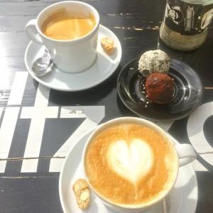 ein Cappuccino mit Herzmuster im Milchschaum, ein Café Crème und zwei Energiebälle