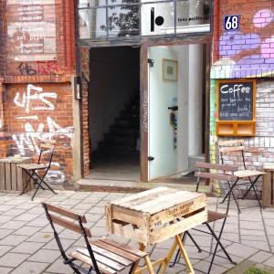 Holzkistentisch und Holzstühle vor dem Eingangsbereich des Less Political Hamburg