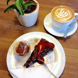 Schokokuchen, Vanilleeis, Erdbeersoße und einer Tasse Cappuccino